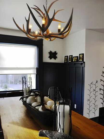 Antler chandelier paired with navy blue wainscoting. An interesting look.