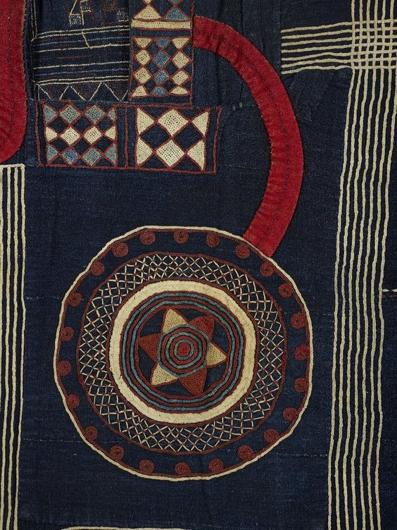 Detail from a Kusaibi gown from the Maninka people of Sierra Leone.  Made from 14 narrow strips of cotton hand-woven on a narrow loom and dyed indigo; hand sewn together. Plain weave; dyed indigo warps and wefts. There is extensive embroidery in dyed cotton and wool over the front and back of the robe in a variety of geometric patterns in white, blue, red and pink.