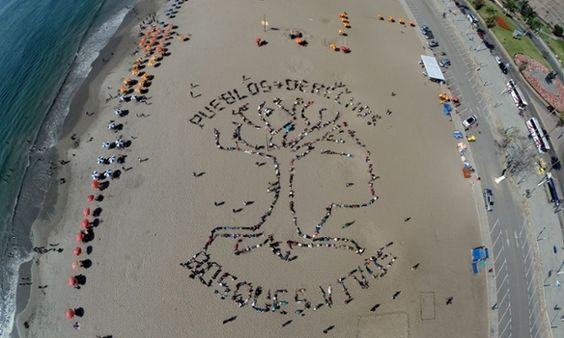 Activists form a human banner on Agua Dulce beach in Lima, with the words 'Indigenous people+rights – living forests'.