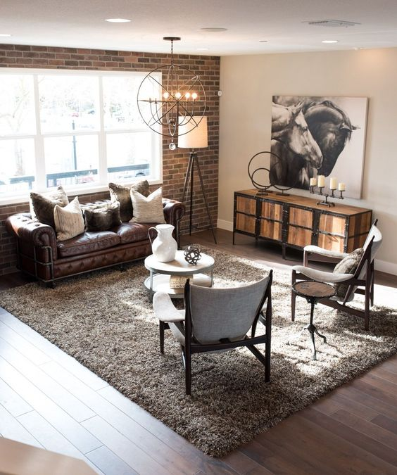 Love: textural brick wall feature. Wooden tripod floor lamp. Metal round industrial ceiling light. Wood and metal console. Focal wall art. Dislike: too neutral. Tufted traditional look of sofa.