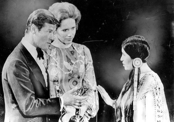 27 March 1973: Roger Moore and Liv Ullman look nonplussed as Sacheen Littlefeather declines the Best Actor Oscar on behalf of Marlon Brando, who was protesting the characterizations of Native Americans in the television and film industries.: