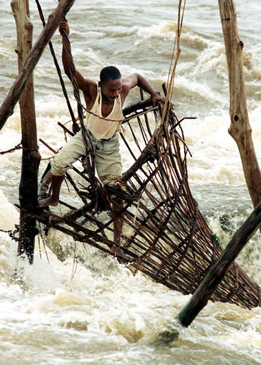 Africa | Sights and Sounds.  A fisherman checks his traps in the rapids upriver from Kisangani. Congo River