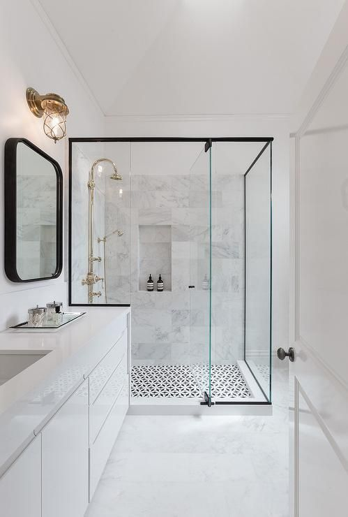 Modern bathroom features a black framed shower enclosure filled with marble tiles fitted with a tiled shower niche as well as a polished nickel vintage gooseneck shower head over a black and white geometric tiled floor.: