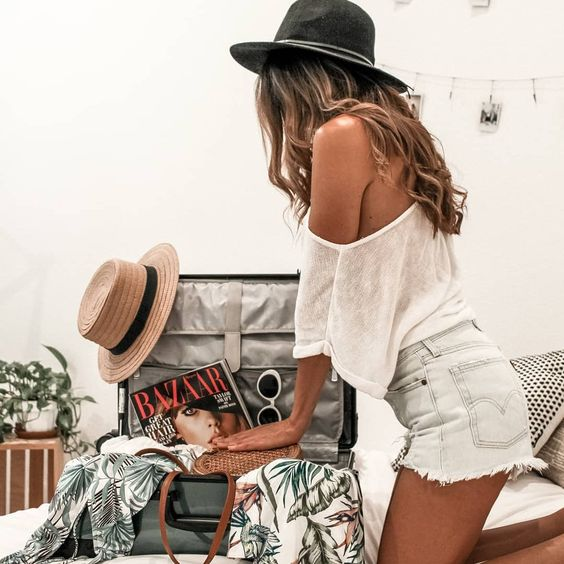 mujer tratando de cerrar su maleta