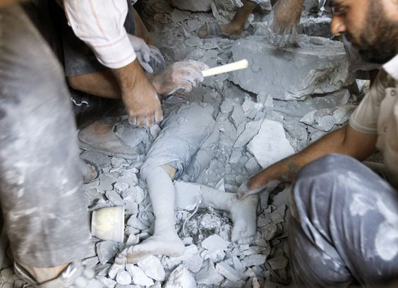 A body of a boy, who was killed by a recent Syrian Air force air strike, is seen under rubble of a house in the village of Tel Rafat, north of Aleppo, August 8, 2012. REUTERS/Goran Tomasevic