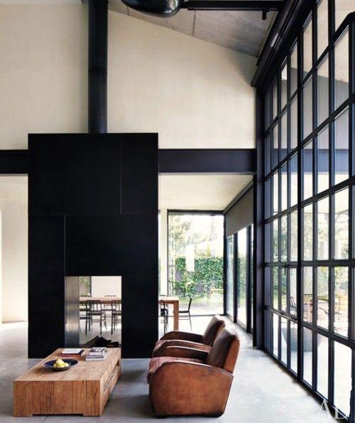 La monumentale cheminée habillée de noir est traversante et s'ouvre d'un côté sur le salon, et de l'autre sur le coin repas.: