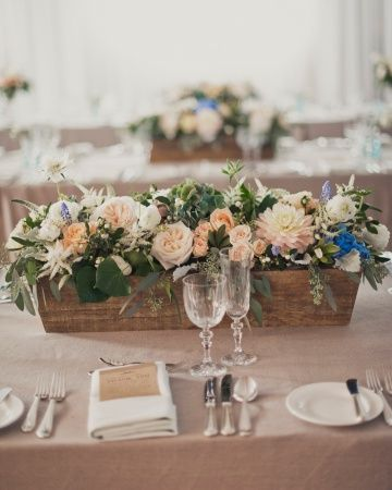 Wooden box centerpieces (hydrangeas, ranunculus, olive leaves, garden roses, and dahlias) paired with mercury glass and candles