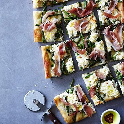 Parmesan, ricotta and lemon zest combine to make an amazing cheesy base for this fun asparagus and prosciutto pizza.
