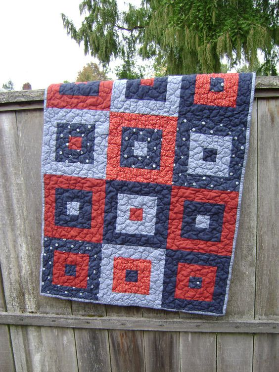 "This bold quilt is just waiting to be loved by some new baby. The strong blues and reds make for a very modern look yet the colors are very traditional for boys. It will fit in many types of decor - nautical, all-american, rustic, athletic or aviation.    The sweet little quilt measures 29"" by 38""."