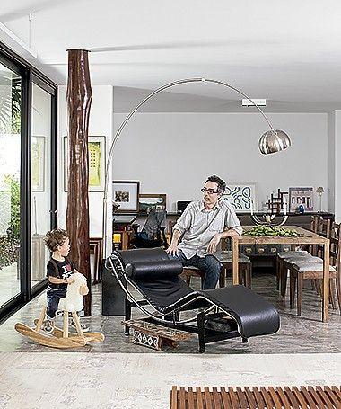 LUZ E ESPAÇOS GENEROSOS Sala de jantar: o arquiteto Carlos Verna e o filho Vito, no balanço da Tok & Stok, junto ao tronco de pau-brasil que sustenta a laje desde a remoção da parede (Foto: Gui Morelli/ Editora Globo)