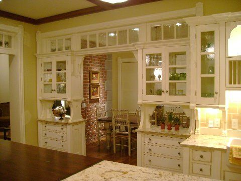Light spilling into the space through the glass cabinetry: Magic House, Practical Magic, Dining Room, Brick Wall, Transom Window