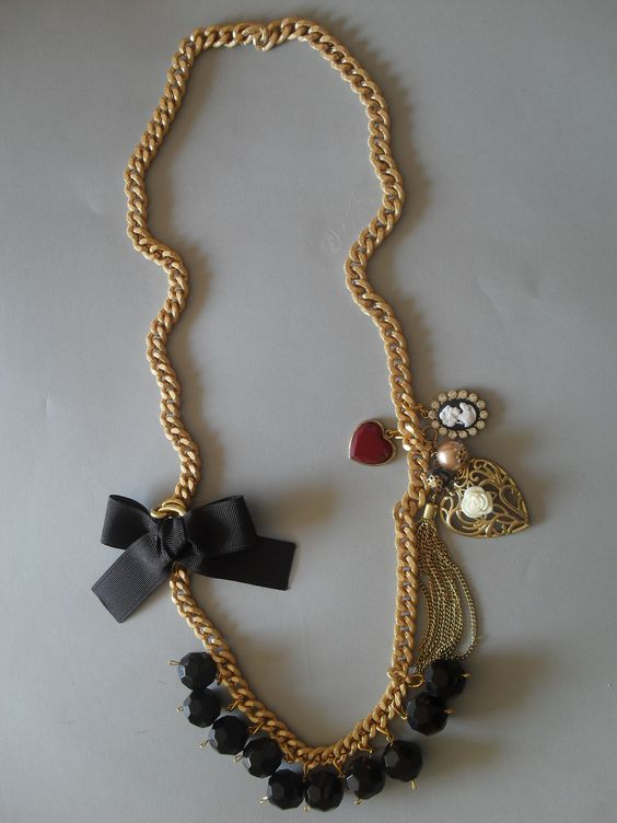 Collar largo dorado con detalle de camafeo, corazones y moño negro