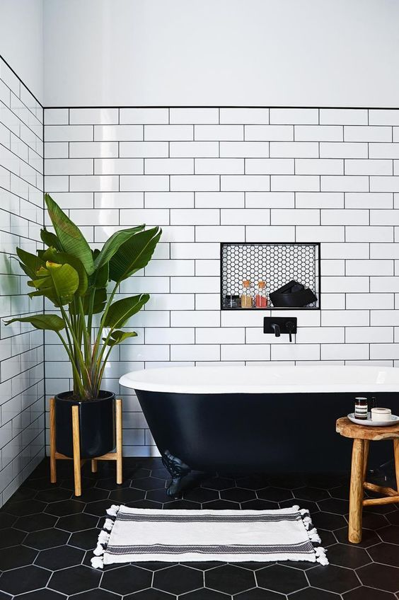 This bathroom is the perfect mixture of black and white to create a modern monochrome bathroom space. I love the floor tiles and the metro wall tiles. The addition of the large plant softens the space with greenery.