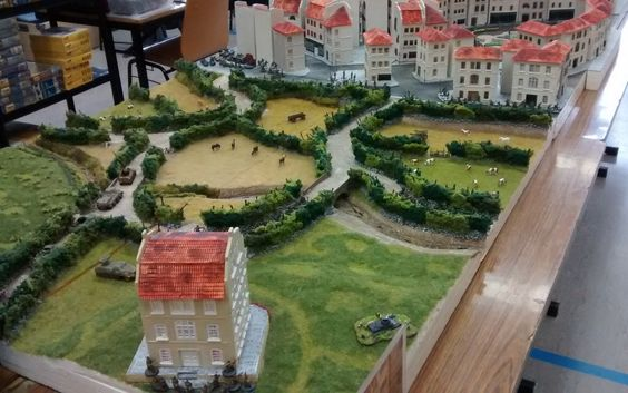 """Hier Schloss """"Le Chateau Tailleville"""" und die verschlungenen Pfade durch die Bocage-Landschaft im hinteren Teil der Dioramenplatte. Auch hier wurde Wert auf eine nicht-rechtwinklige sondern geschwungene und harmonische Linienführung gelegt. Links zu erkennen ist der Sperrbereich vor dem Regelbau 272, der durch Minenfelder und Stacheldraht-Hindernisse gesichert ist. Der Bach zieht sich quer durch die gesamte Bocage-Landschaft und birgt dank Plastis Einfallsreichtum so einiges an optischen…"""
