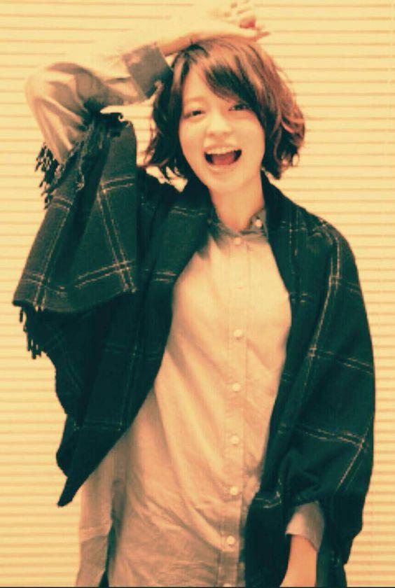 グリーンのストールを羽織って笑っている小林涼子の画像