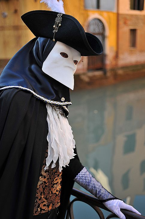 Bauta mask, photo by Alain Boussac. ong considered the traditional and archetypal Venetian mask, the Bauta always used to appear in white, and even though it was worn extensively throughout the Carnival period it owes much of its prominence to the fact that it was used all year round by those simply wishing to hide their identity. It was also a comparatively practical mask, since, lacking a mouth and covering only the upper half of the face, it enabled masqueraders to eat and talk more freely: