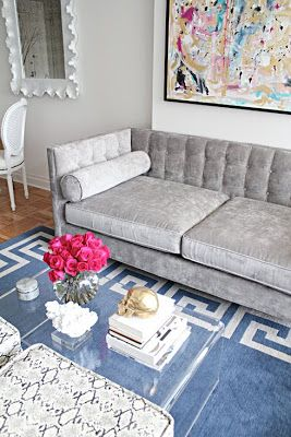 Jen Ramos living room (madebygirl.com) : grey tufted velvet sofa, greek key rug, lucite coffee table, python x-benches
