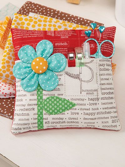 "This sweet pincushion has a padded pocket for all the extras that you may need when you are sewing. Slip a small pair of scissors inside with other supplies like thread and a ruler, and use the edge to hold clips. Finished size: 6"" x 6"" x 2..."