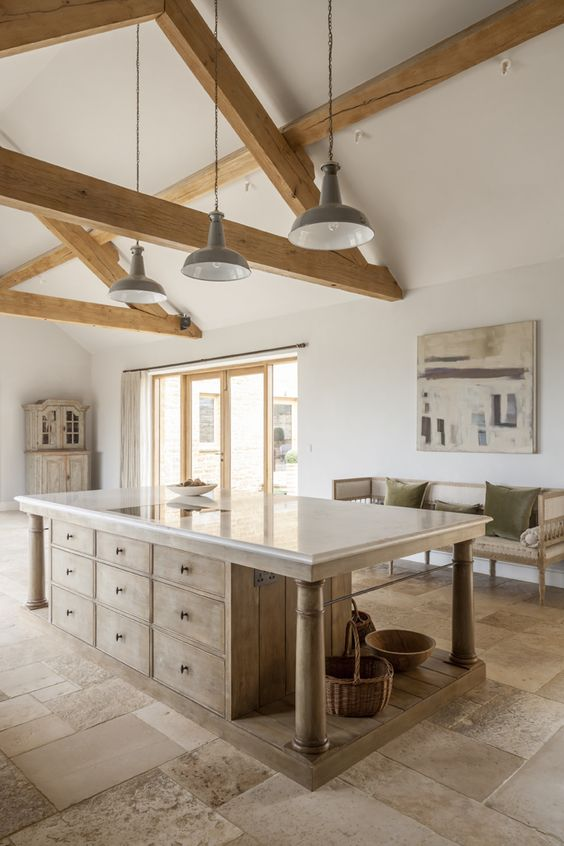 A bespoke modern rustic country kitchen by Artichoke with large island. This bespoke modern rustic kitchen, designed for a new build country house, takes influence from Flemish design. The large central kitchen island has a specialist finish to age the material and give it a rustic feel. The painted furniture forms a backdrop to the island and has classical detailing with raised and fielded panel doors.Primary materials: Oak, Bental White marble, hand painted furniture and bronze handles #bespoke #kitchendesign #englishcountry #englishkitchen #flemish #modernrustic