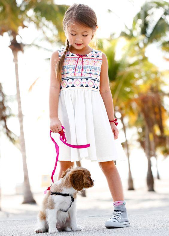 Jetzt anschauen: Cooles Kleid für kleine Trendsetter. Vorne am Brustbereich mit schickem Muster bedruckt. Mit kleinen Bommeln und einer kleinen Schleife verziert. Fällt in leichter A-Linie.