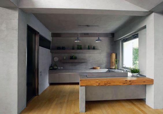 Uno stile elegante e moderno declinato nel grigio del cemento mescolato a inserti fatti di altri colori e materiali. Anche la cucina è in cemento armato attraversato dai piani e le lampade in acciaio inox. Una trave di legno di castagno è utilizzata come piano di lavoro