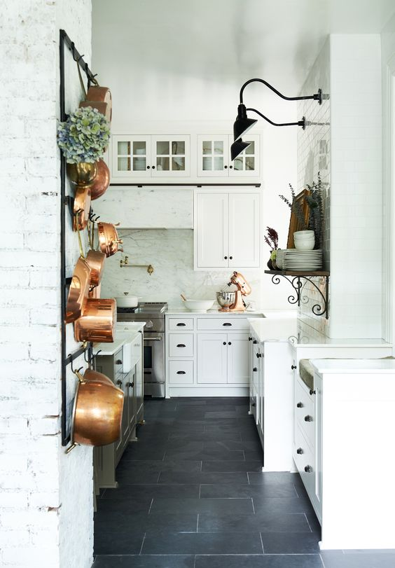 White kitchen design with black slate tile flooring, white cabinetry, black barn style lighting, white brick, and copper pots. Restored By The Fords - Leanne Ford Interiors - The Donley Project - Shot by Alexandra Ribar