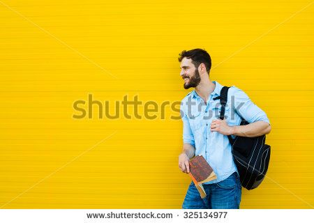 handsome student with backpack standing outside on yellow background