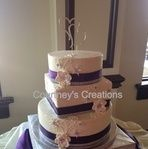 Mixed round and square bling wedding cake with edible flowers and purple ribbon.