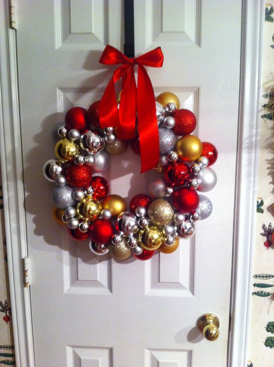 """Buy ornaments (I used 50-60 plastic ones from Garden Ridge) and a 14"""" styrofoam wreath. Take the hangers off the ornaments and stick into the wreath to make the initial hole, then hot glue them. I started in the center and worked outward. Fill in gaps with smaller ornaments and hang with thick ribbon. It took about 30 minutes."""