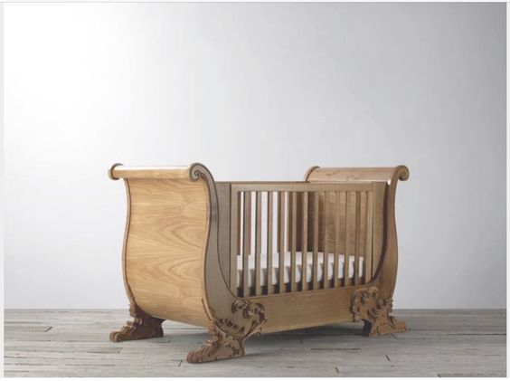Cot bed with carvings at ends