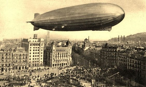 The Graf Zeppelin over Plaça  de Catalunya, Barcelona 1929. Probably a fake of that time, zeppelins were in fashion and postcard makers added zeppelins to the sky. In this case the dirigible is too low to be safe over  a built area. And it's too small, is should be as long as the square!