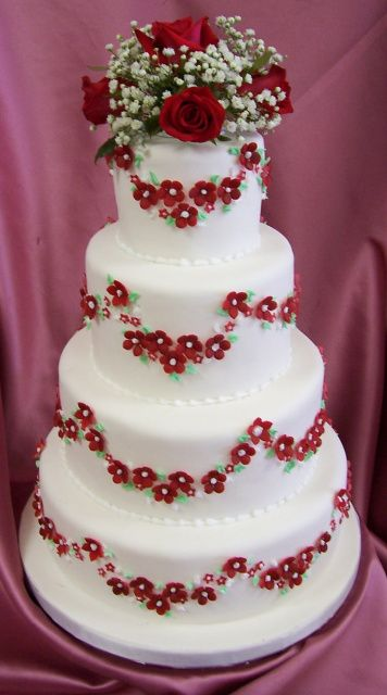 white wedding cake with little red flowers, roses & babies breath on top