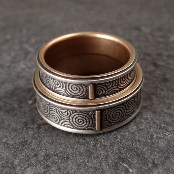 These beautiful wedding bands are made from sterling silver and 14k gold. To make this ring, each band was inlaid with a ribbon of