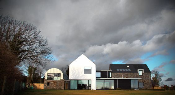Rural replacement dwelling located outside Belfast 3 familiar vernacular forms - the curved Barn, the white Farmhouse and the stone Out House.   Designed by BGA Architects Ltd