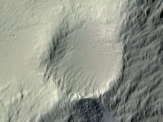 A piece of Mars: In the center of this image is a 270 m crater (885 ft) that was nearly buried, along with the surrounding terrain, by dust. Since then, wind from the upper left has scoured the dust deposit, forming streamlined horse-tail shapes. A few meter-scale boulders, possibly flung in from nearby impacts, show the most recent streamlined erosion. (ESP_035994_1805, NASA/JPL/Univ. of Arizona)