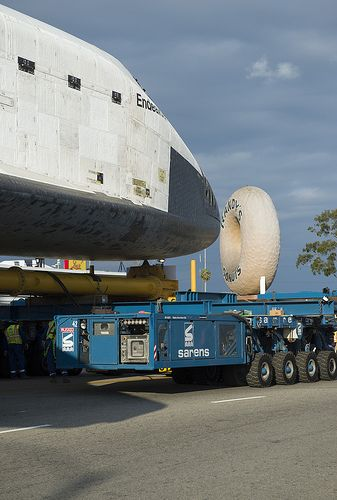 The nose cone of the space shuttle Endeavour is seen next to the Randy's Donuts landmark in Inglewood, California, Friday, Oct. 12, 2012. Space Shuttle Endeavour Move (201210120007HQ)