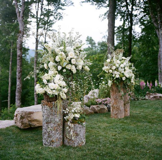 Backyard wedding altar - pretty floral arrangements on cut logs. Photo: A Bryan Photo / Event Planning & Design: Mariee Ami / Event Design, Floral Design: Wildflower Designs