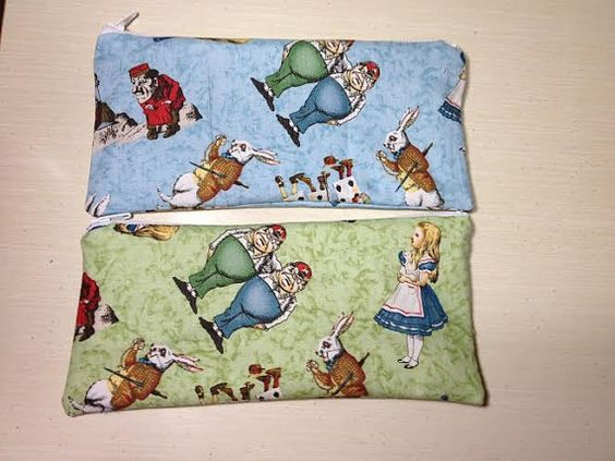 This is a Alice in Wonderland print coin purse with zipper top closure. fully lined with fabric. Size is approximately 4 x 5 inches (not