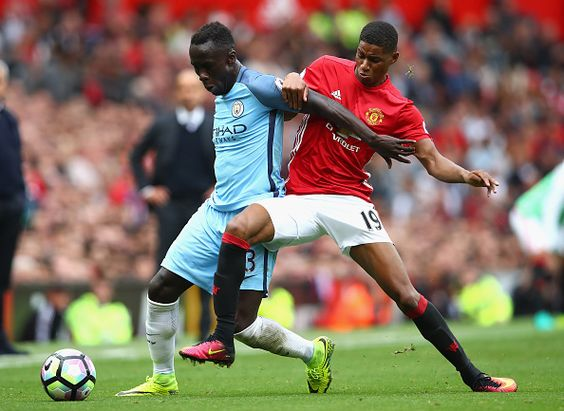 Bacary Sagna of Manchester City is tackled by Marcus Rashford of Manchester…