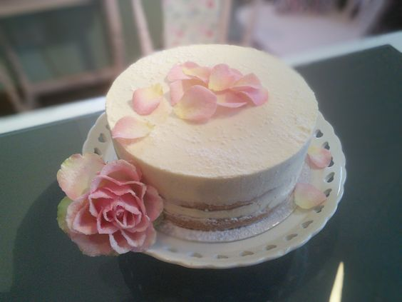 Classic vanilla bean Victoria sponge naked cake, decorated with sugared rose petals.
