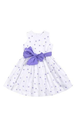 Vestido para niña en tela estampada con florecitas moradas sobre fondo blanco. Cuello redondo y sin mangas.