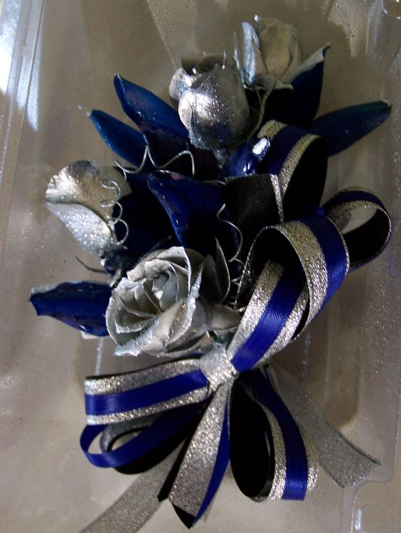 white roses with royal blue and silver ribbons in this