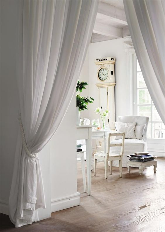 Curtains as a room divider in a hallway. Scandinavian decor in a white living space. Beautiful Classically Refined Rooms
