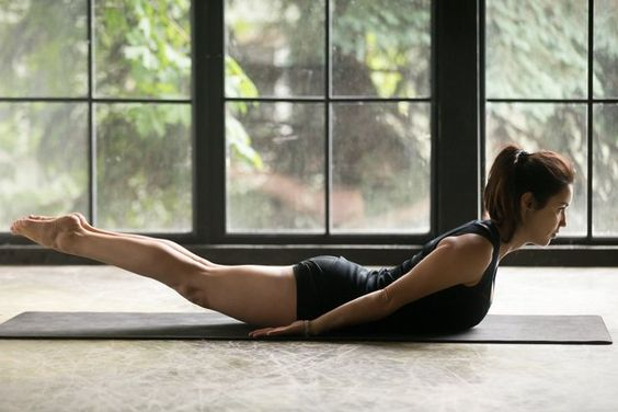 Woman holding locust pose on mat in front of window.