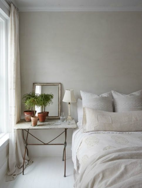 Soft and serene creamy white bedroom with vintage French table and linens.