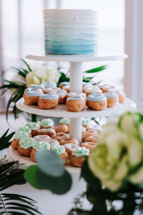 Elegant Tropical Coastal Blue and Green Wedding Reception Dessert Table with White and Blue Ombre Single Tier Round Wedding Cake and Light Blue and Seafoam Green Frosted Mini Doughnuts on Three Tiered White Cake Stand, with Natural Coastal Greenery and Blush Rose Flower Arrangements in Low Round Glass Vases | Tampa Bay Wedding Cake Bakery The Artistic Whisk