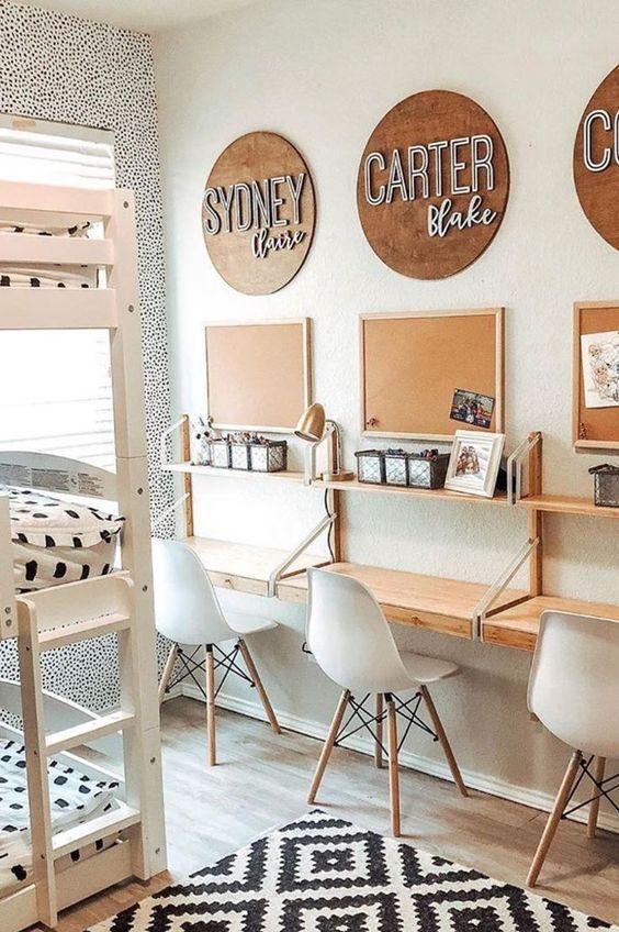 Tres escritorios para niños, en tonos madera y blanco.