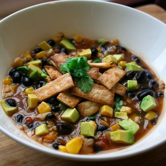 Healthy Hearty Mexican Style Soup - Vegetarian Recipe.   An amazing combination of corn, brown rice, and black bean seasoned with Mexican spices and toped with toasted tortillas and avocado.  Nutritional information included in the recipe.