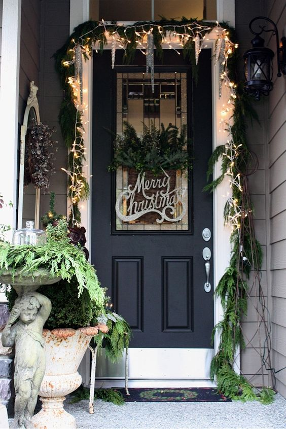 Christmas front door with white lights, greenery, and vintage accessories