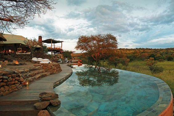 Faru Faru River Lodge is built on a sloping hill above a beautiful water hole and the Grumeti River. A modern interpretation of a traditional Maasai home, the lodge blends unobtrusively into the landscape.